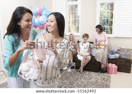 Woman showing gift at baby shower - stock photo
