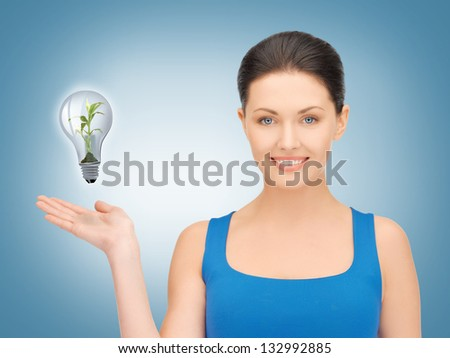 woman showing green light bulb on her hand