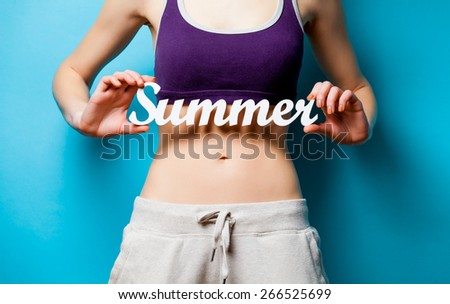 Woman showing her abs with Summer word inscription after weight loss on blue background - stock photo