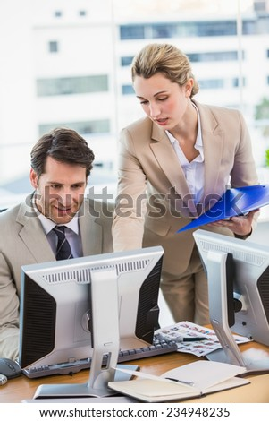 Woman showing her colleague something on the screen at work - stock photo