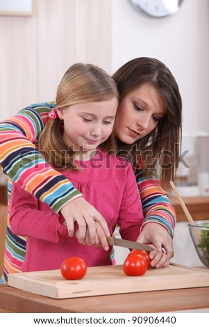 Woman showing her daughter how to cut a tomato - stock photo