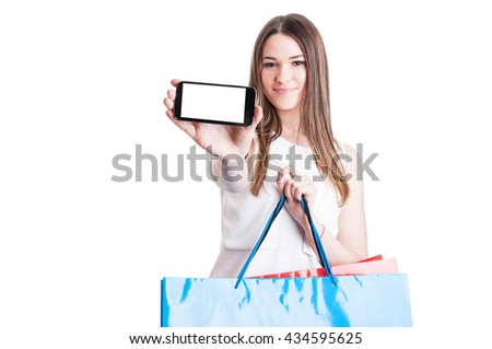 Woman showing her mobile phone with empty screen while doing shopping isolated on white with copyspace - stock photo