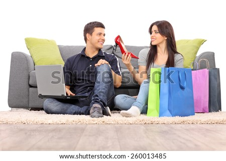 Woman showing her new shoes to her boyfriend isolated on white background - stock photo
