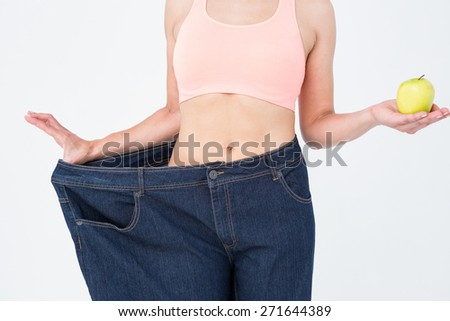 Woman showing her waist after losing weight on white background - stock photo