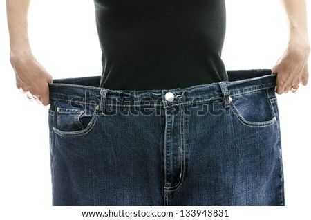 Woman showing how much weight she lost by wearing her old jeans. Weight loss concept. - stock photo