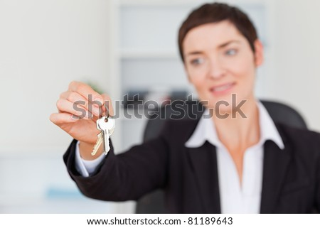 Woman showing keys with the camera focus on the keys - stock photo