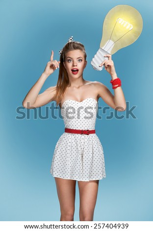 Woman showing light bulb banner looking happy excited / sexy young American pin-up girl on blue background having idea  - stock photo