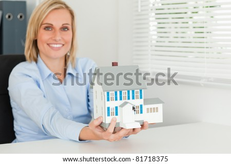 Woman showing model house in her office - stock photo