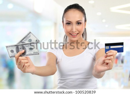 woman showing  money and credit card in shopping mall - stock photo