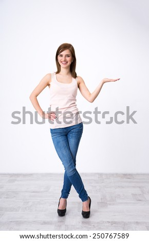 Woman showing product - empty copy space on the open hand palm - stock photo
