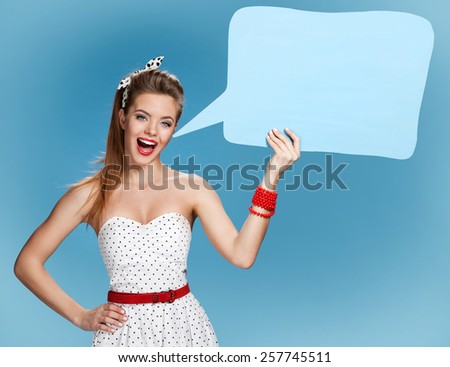 Woman showing sign speech bubble banner looking happy excited / Beautiful young American pin-up girl on blue background - stock photo
