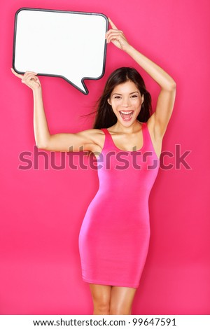 Woman showing sign speech bubble with copy space. Beautiful excited smiling happy joyful mixed race Asian / Caucasian female fashion model in pink dress on pink background. Energetic and fresh photo. - stock photo