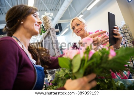 Woman Showing Something On Digital Tablet To Florist - stock photo