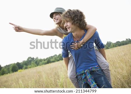 Woman showing something while enjoying piggyback ride on man in field - stock photo