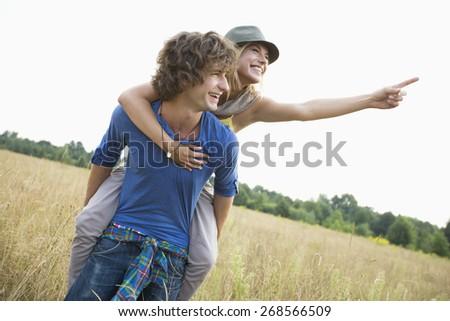 Woman showing something while enjoying piggyback ride on man in field - stock photo