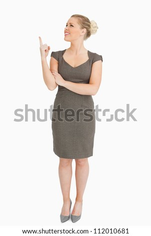 Woman showing something with her finger against white background - stock photo