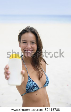 woman showing suncream at the beach smiling - stock photo
