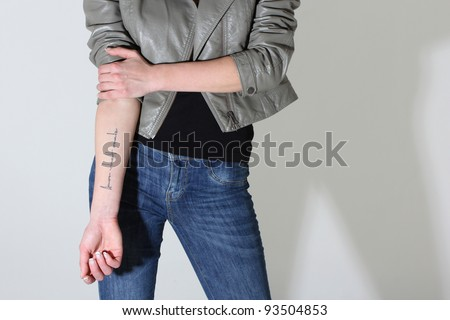 woman showing tattoo on her hand over grey