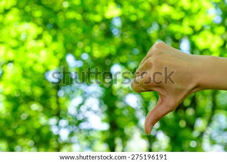 Woman showing thumbs down on natural green background - stock photo
