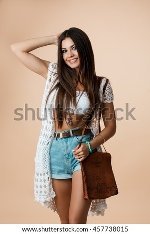 Woman showing thumbs up, everything is OK, everything is super! Going on vacation the dress of the summer for vacation,Jean shorts, black crop top, necklace from wood. Fashion trend beauty lady smiles - stock photo