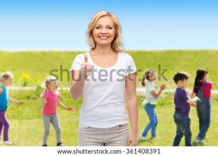 woman showing thumbs up over group of little kids - stock photo