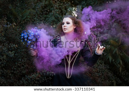 Woman showing tricks with a magic wand. She bewitched a bouquet of flowers from which it is purple smoke. - stock photo