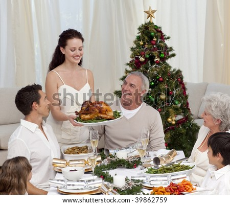 Woman showing turkey to her family for Christmas dinner - stock photo