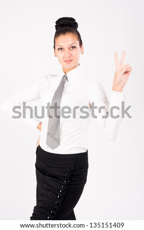 Woman showing victory gesture at isolated background - stock photo