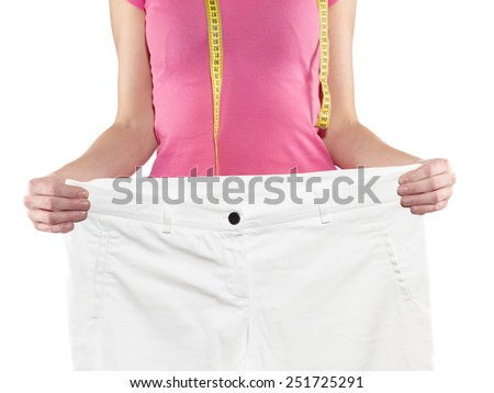 Woman shows her weight loss by wearing an old big trousers. Weight loss concept. - stock photo