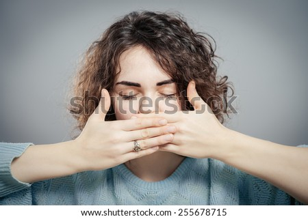 Woman shutting her mouth - stock photo