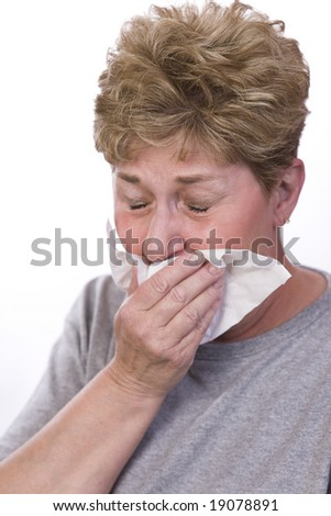 woman sick with a cold covers her mouth to cough - stock photo