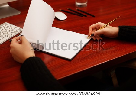 Woman signing a document or writing correspondence with a close up view of his hand with the pen and sheet of notepaper on a desk top. Folded sheet of paper - stock photo