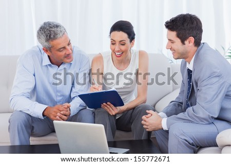 Woman signing contract as husband and salesman watch sitting on couch