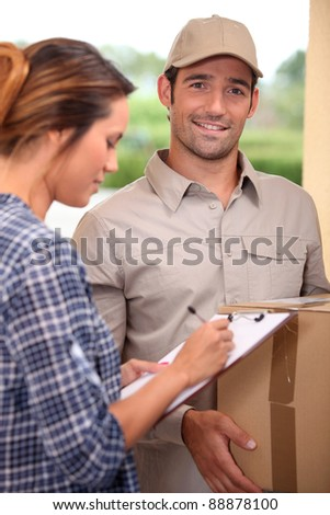 Woman signing for a courier delivered parcel - stock photo