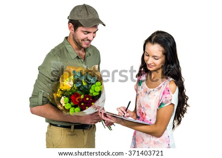 Woman signing for bouquet delivery with smiling postman on white screen - stock photo