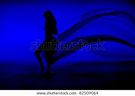 Woman silhouette at blue background, waving dress as wings on a wind flow