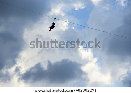 Woman silhouette high-speed sliding via zip-line against cloudy sky.