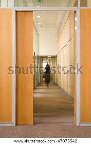 Woman silhouette in corridor of office building - stock photo