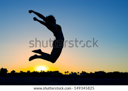Woman Silhouette Jumping on the Beach at Sunset transmitting a concept of health, joy and freedom
