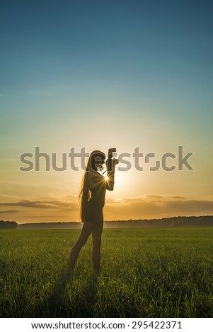 Woman Silhouette of Young adult female Photographer silhouette at Sunset light rays Cute girl hold professional digital camera with flash against blue and yellow sky background  - stock photo