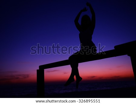 Woman silhouette on sunset sky background - stock photo