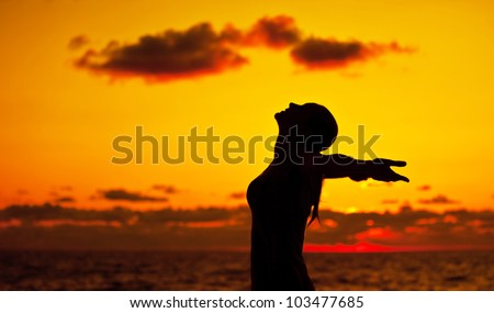 Woman silhouette over sunset sky, dark black shadow of female body with hands up, teenage girl having fun outdoor, enjoying sundown on the beach, freedom lifestyle, happiness concept - stock photo