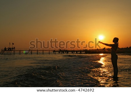 woman silhouette praying to sun at sea coast