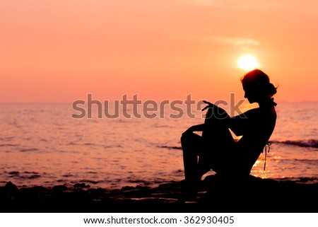 Woman silhouette sitting on sunset sea background, side view, back lit