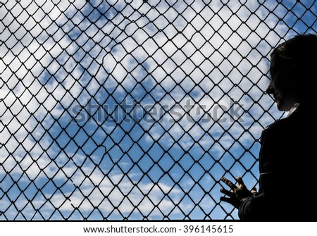 woman silhouette stand near black metal Net against blue sky with clouds - stock photo