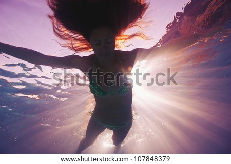 Woman silhouette underwater in swimming pool with back light.