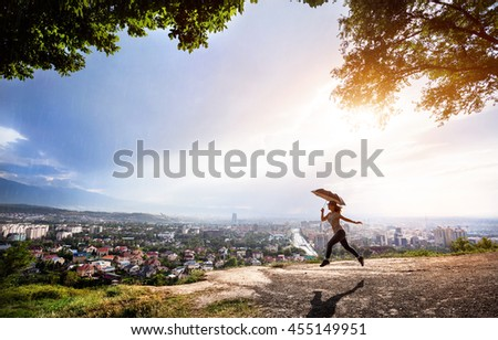 Woman silhouette with umbrella jumping over the view to city panorama at rainy dramatic sunset.