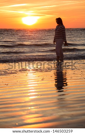Woman Silhouetted by the Setting Sun Takes a Stroll on the Beach - stock photo
