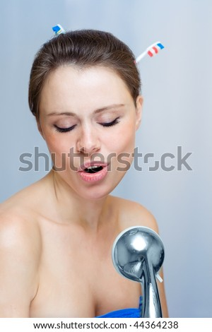 Woman singing in the shower with tooth brush in the hair - stock photo