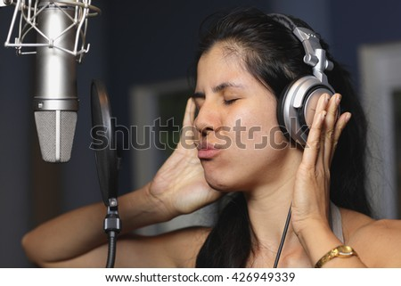 Woman singing in the studio - stock photo